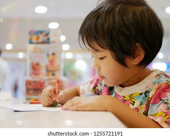 Little Asian baby girl learning to grasp a crayon and do painting by herself