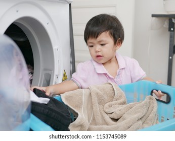 Little Asian baby girl removing dried clothes from an electronic dryer - baby's development through allowing them to help doing housework