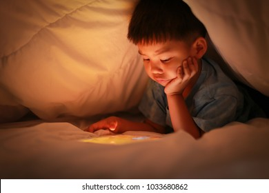 Little asian boy attention on online device while lying under white blanket in the bedroom at night, bright screen light reflex on kid face. Learning concepts of internet and technology for children.