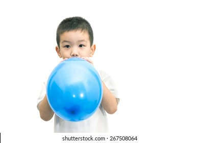 Little asian boy blowing a blue balloon isolated on white background