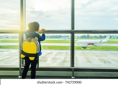 Little Asian boy carry bag waiting boarding to flight in airport transit hall and looking through the window at airplane departure. Active family lifestyle, travel by air with child on summer vacation