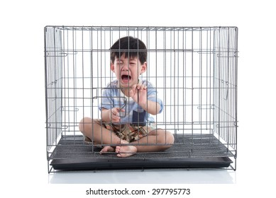 Little asian boy crying in a cage on white background isolated
