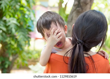 Little asian boy crying while mother holding him to go to school