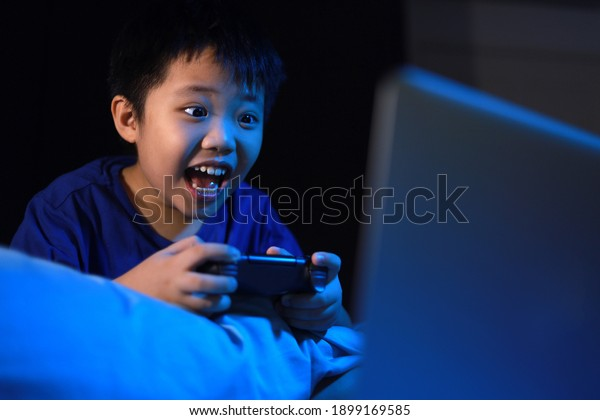 Little Asian boy in dark bedroom playing a console video game. Soft focus image. Blue light effect.