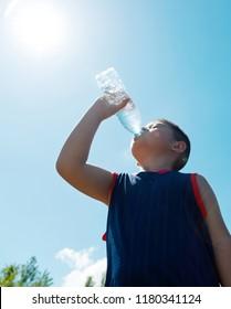 Little asian boy drinking water against blue sky.