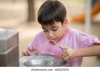 Little asian boy drinking water in the public park