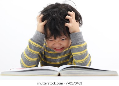 Little Asian boy frustrated over homework with his both hand on head.. Boy studying at table isolated on white background.