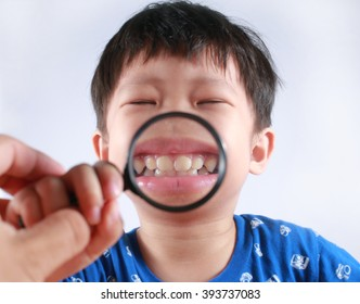 Little Asian boy with funny big teeth exploring using using magnifying glass