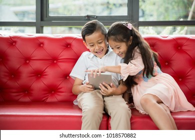 Little asian boy and girl enjoy playing computer tablet or smartphone on red sofa