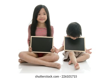 Little asian boy and girl sitting and holding  chalkboard on white background isolated