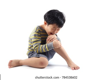 A little Asian boy have injured his leg and suffering knee pain sitting on the floor.