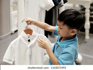 The little Asian boy holding coat hanger and checking polo shirt. Background with many kid shirt hanging in closet. concept of buy, sell and kid clothes fashion .
