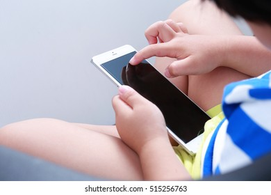 Little Asian boy at home using smart phone