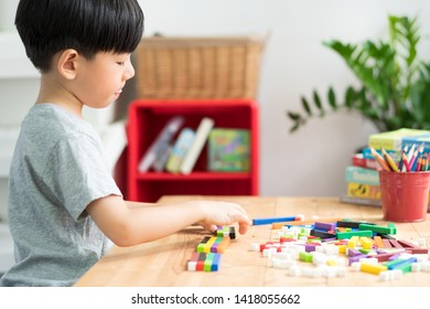 A little asian boy learning about numeracy, adding - subtracting and counting through colorful cuisenaire rods. Early math, Cognitive skills, Learning tools, Child development concept.
