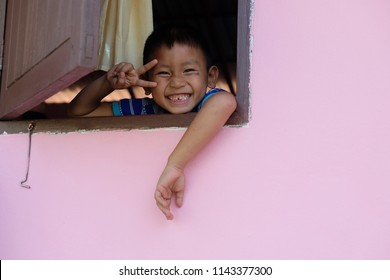 Little asian boy Looking out the window and show his hand with big smile.