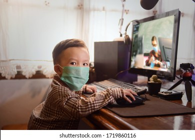 Little asian boy with masks using pc computer to studying . selected focus on one eye with blurred background,vintage style