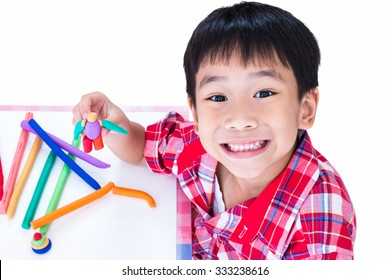 Little asian boy playing and creating toys from play dough. Child smiling and show his works from clay, on white background. Strengthen the imagination of child