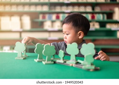 little asian boy playing and sorting wooden tree toy