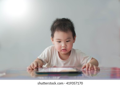 Little asian boy playing tablet , focus on face