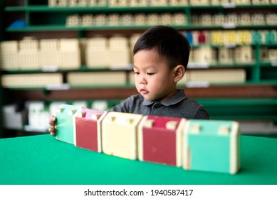 little asian boy playing wood building tower block toy