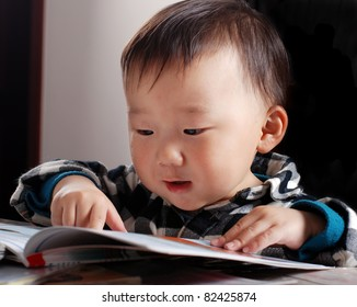 little asian boy reading book
