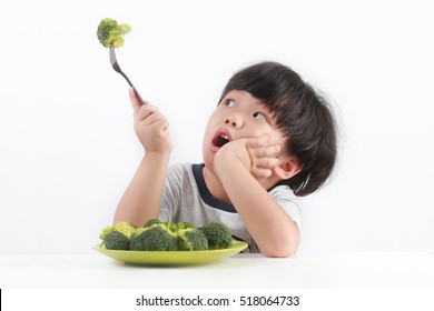 Little Asian boy refuse to eat healthy vegetables.