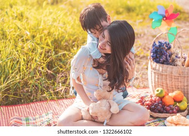 Little Asian boy riding back on his super power mom in meadow when doing picnic. Mother and son playing together. Celebrating in Mother day and appreciating concept. Summer people and lifestyle theme.