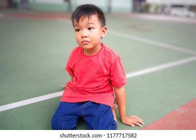 A little asian boy is sitting in the basketball court. He made a sad face and tried.