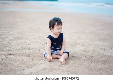 little asian boy sitting on the beach of Thailand