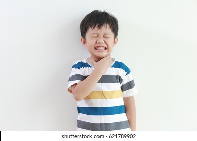 Little Asian boy with sore throat touching her neck, feeling pain in her throat.