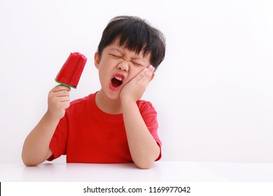 Little asian boy suffering from toothache while eating ice pop - Dental problem.