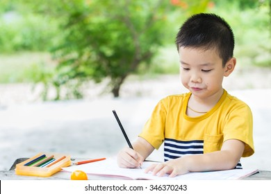 Little asian boy use pencil writing on notebook for writing book with smiling face on wooden table in the park
