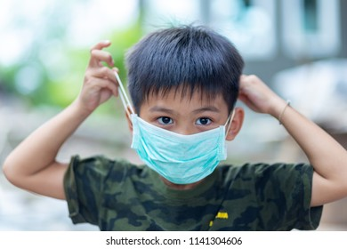 little Asian boy wearing a protective mask , illness prevention , health care concept