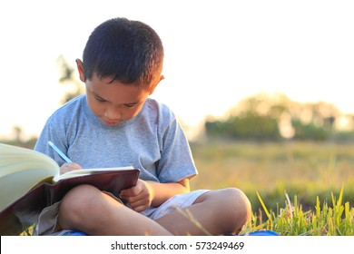 Little asian boy writing book with pencil in the park on sunset