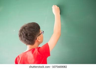 Little asian boy writing on empty green board at school