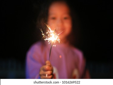 Little Asian child girl enjoy playing firecrackers. Focus at fire sparklers.