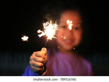 Little Asian child girl enjoy playing firecrackers.