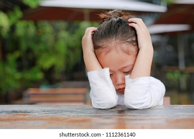 Little Asian child girl expressed disappointment or displeasure on the wood table.