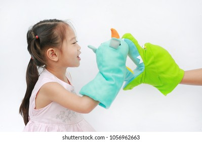 Little Asian child girl hands playing animal puppets with hand of her mother on white background. Educations concept.