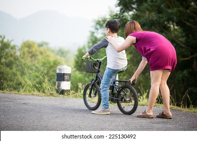 little Asian child with mother practice to riding a bicycle at the park