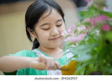 Little Asian child planting flower