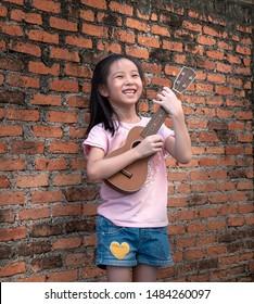 Little asian child play the ukulele, old brick wall background