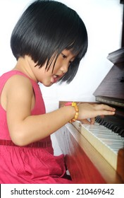 little asian child playing the piano and sing