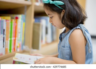 Little Asian child reading a book on the library