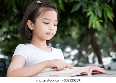 Little Asian child reading a book outdoor