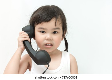Little asian child with telephone. Happy young girl talk to call phone on white background. Asia kid holding phone and eye contact.