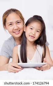 Little Asian child using tablet with mother