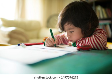 Little Asian Chinese boy child kid writing and drawing on a table. Preschooler. Early learning. Kindergarten homework. Homeschooler art class. Playschool at home. Gifted student. Day activity.
