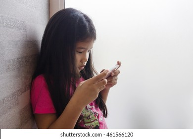little Asian cute black hair girl wearing pink shirt looking, using mobile smart phone at white glass window with copy space for text in cozy home : people and technology concept
