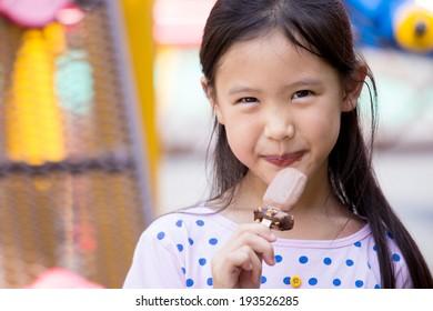 Little Asian cute child enjoy eating ice-cream near the playground